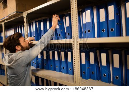 Businessman taking file from shelf in storage room at workplace
