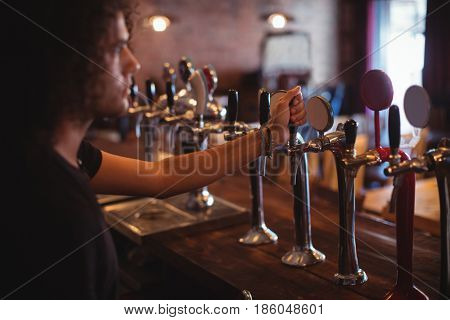 Male bar tender at bar counter in pub