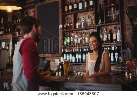Female bar tender interacting with customer at bar counter