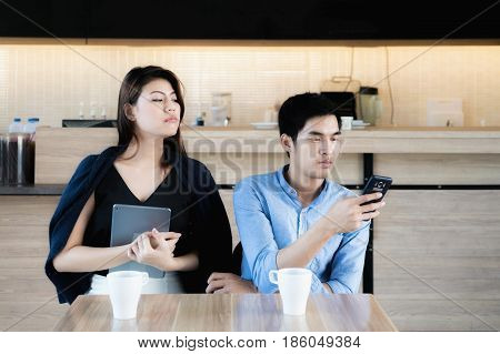 Young Asian lover couple using smartphones at cafe. Jealous girlfriend peeking for spy her boyfriend's phone. Love and jealous concept.