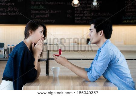 Asian man showing an engagement ring diamond to his amazed girlfriend in a restaurant. Proposal concept