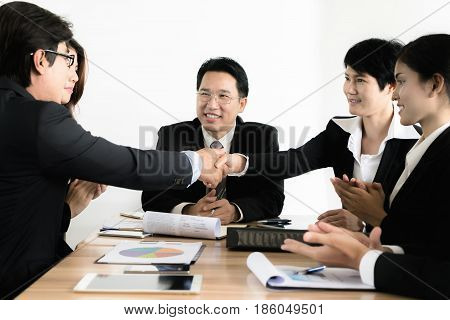 Asian businessman and businesswoman shaking hands in conference room. Business people shaking hands agreement concept.