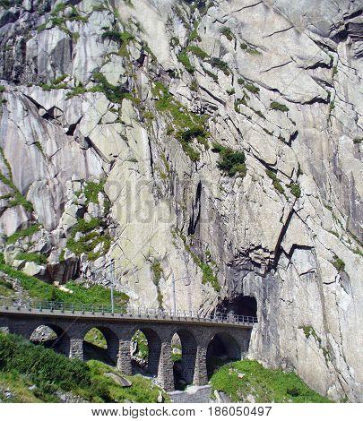Railway bridge and tunnel in Switzerland near village Andermatt.