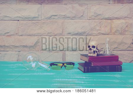 safety eye glasses and skull on old book