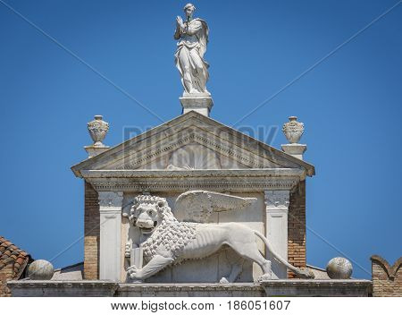 The winged lion of St. Mark on top of The Porta Magna at the Venetian Arsenal. Is the symbol of the city of Venice in Italy and is often seen holding a book representing power, wisdom and justice