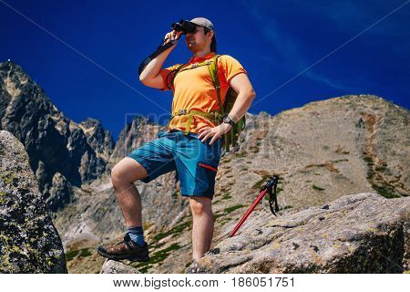 Young man tourist with green backpack looking in binoculars on high mountains