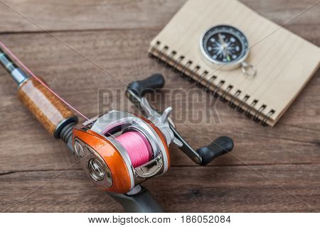 Fishing tackle - Baitcasting Reel book and compass on wooden background