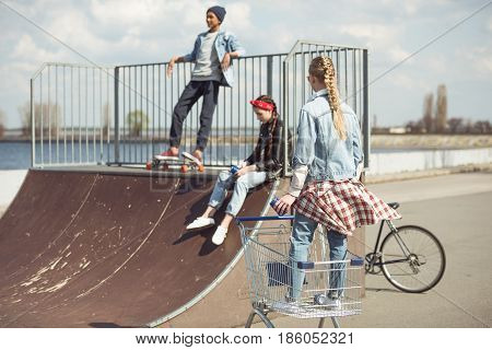 Blonde girl standing in shopping cart while friends resting on ramp at skateboard park