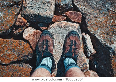 Man tourist shoes on stone surface close-up view