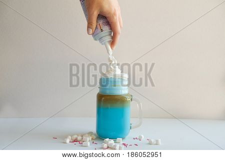 Girl is adding cream in stylized mason jar cup of colored blue milk. Milk shake cocktaill frappuccino. Unicorn coffee unicorn food.