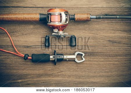 Fishing Tackle - Baitcasting Reel, Gripper On  Wooden Background