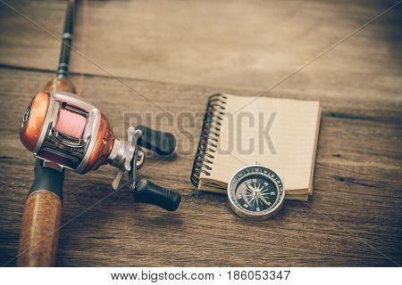 Fishing Tackle - Baitcasting Reel, Book And Compass On  Wooden Background
