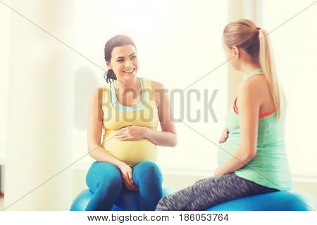pregnancy, sport, fitness, people and healthy lifestyle concept - two happy pregnant women sitting and talking on balls in gym