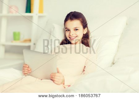 people, children, rest and technology concept - happy smiling girl lying awake with tablet pc computer in bed at home