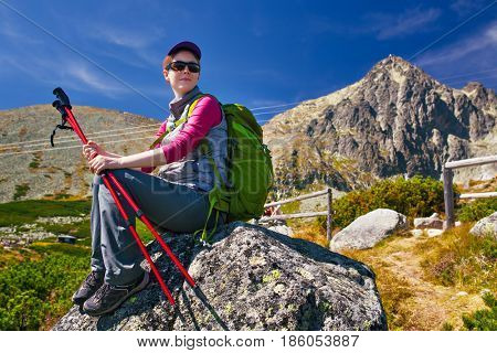 Young woman tourist with green backpack and poles sitting on high mountains background