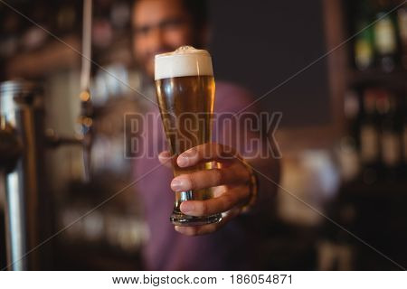 Male bar tender giving glass of beer at bar counter