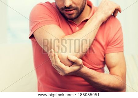 people, healthcare and problem concept - close up of man suffering from pain in hand or elbow at home