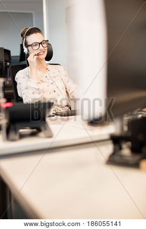 Smiling businesswoman talking on headset while sitting at office