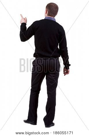 Back view of pointing business man. gesticulating young guy in black suit. Rear view people collection.  backside view of person.  Isolated over white background.