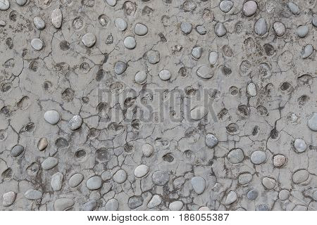 A grey wall with coarse large pebbles