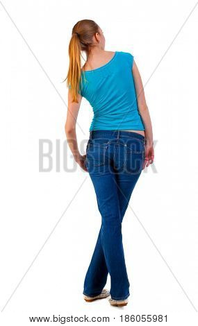 back view of standing young beautiful  blonde woman in blue t-shirt and jeans. girl looks in a relaxed position in  side.  backside view of person.  Isolated over white background.