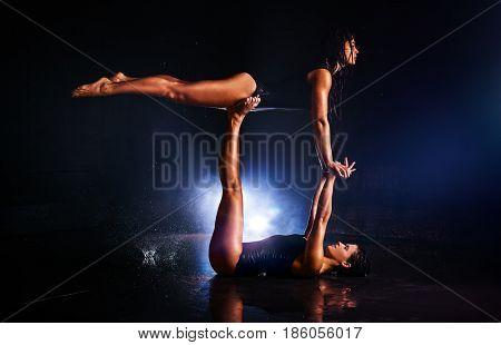 Two women gymnasts doing acrobatic trick in water studio