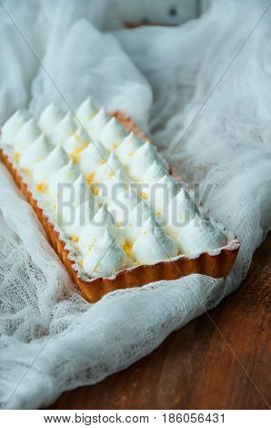 Lemon tart with wipped double cream frosting on a wooden board. Toned.