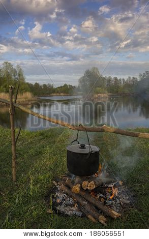 Black pot are heating under fire. Water trees and sky in background.