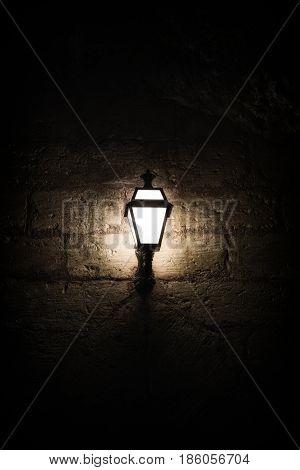 A luminous lantern on a stone wall