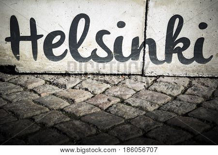 Helsinki sign on kerb by typical cobbled paving in the Finnish capital