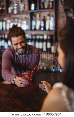 Male bartender serving a cocktail drink to customer at bar counter
