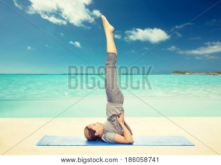 fitness, sport, people and healthy lifestyle concept - woman making yoga in shoulderstand pose on mat over beach background