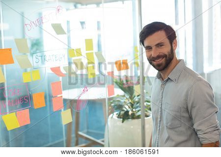 Portrait of smiling businessman standing by adhesive notes on glass at office