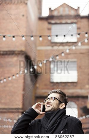 Young smiling man in glasses talking on smartphone outdoors