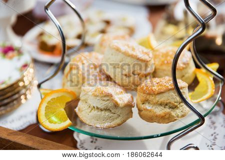 food, junk-food, culinary, baking and eating concept - close up of sweet sugared buns on stand