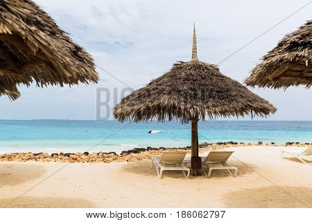 travel, tourism, vacation and summer holidays concept - palapa and sunbeds on exotic tropical beach