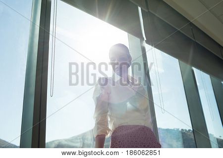 Low angle view of businesswoman standing by brightly lit window in office