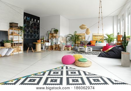Modern apartment with colorful poufs sack chair and pattern carpet