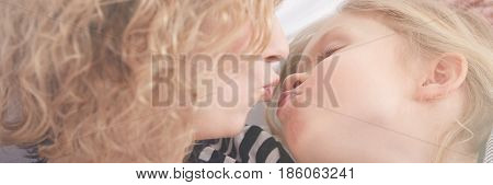 Mother Giving Kiss To Daughter