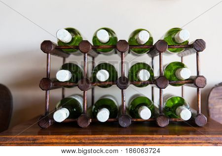 storage, winery and alcohol drinks concept - white wine bottles stored on wooden rack