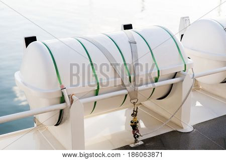 shipping, rescue and sailing concept - life raft container on ship or boat deck