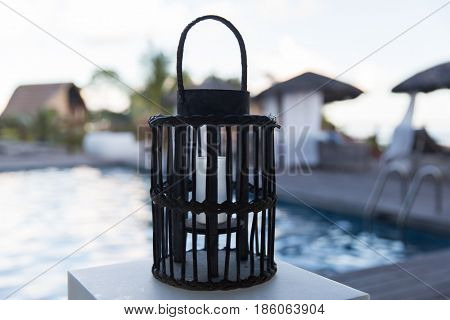 light and summer holidays concept - lantern with extinct candle at outdoor swimming pool