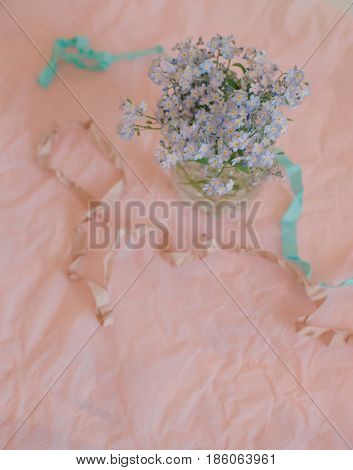On a pink tablecloth vase with a bouquet of forget-me-nots and a ribbon