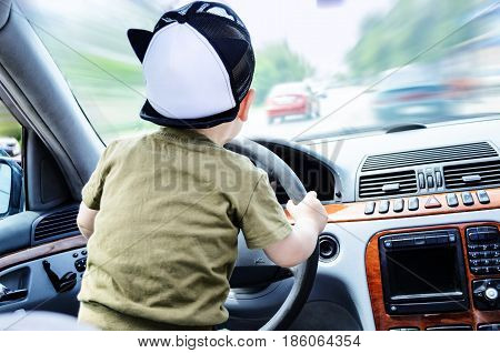 Child racer. Little boy is driving a car at high speed. Blurred cars on the road