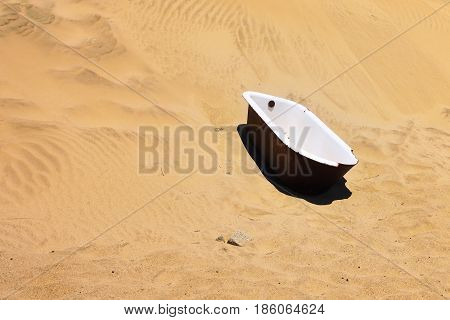The abandoned bathtub in the sand desert in the ghost diamond town of Kolmanskop in Namibia which is slowly being swallowed by the desert poster