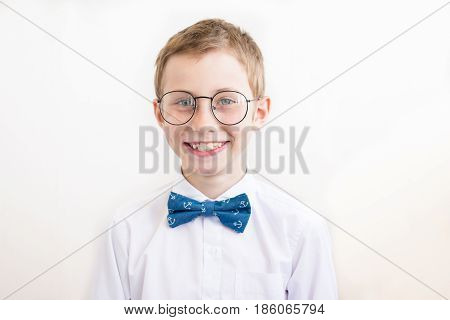 Smiling boy with glasses in white shirt with butterfly on a white background