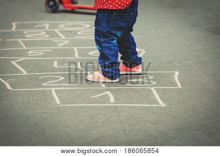 little girl playing hopscotch at playground outdoors