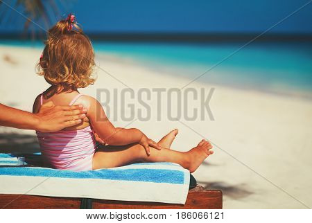 sun protection concept-mother applying sunblock cream on child shoulder