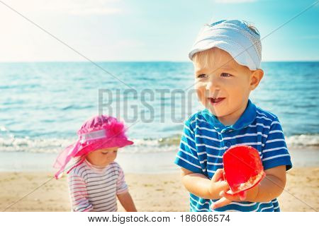Babygirl and babyboy playing on the beach in summer