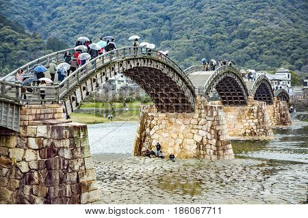 JAPAN, IWAKUNI, APRIL, 03, 2017 - Old Kintai Bridge, unique wooden arch bridge on stone pillars spanning a river Nishiki in the city of Iwakuni, at Yamaguchi Prefecture, Japan.